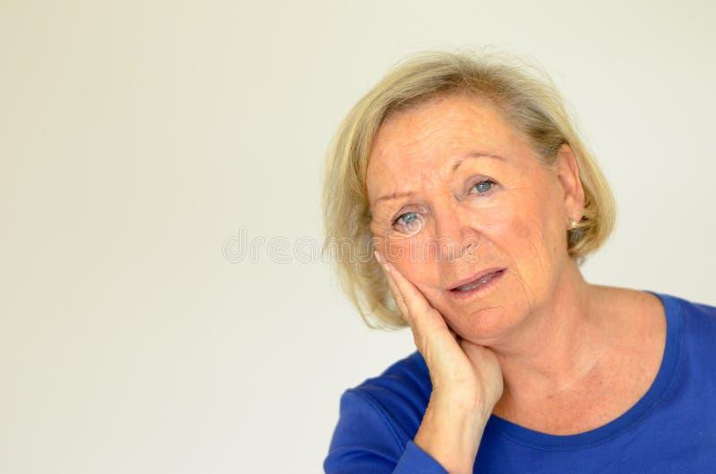 Signora anziana preoccupata che esamina la macchina fotografica immagini stock