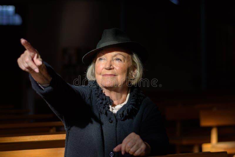 Signora anziana privata che prega in una chiesa immagine stock
