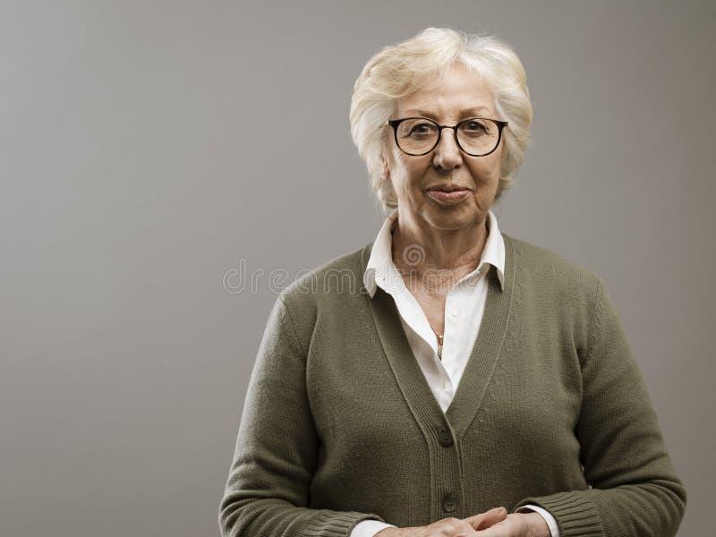 Signora anziana serena che posa sul fondo grigio fotografia stock
