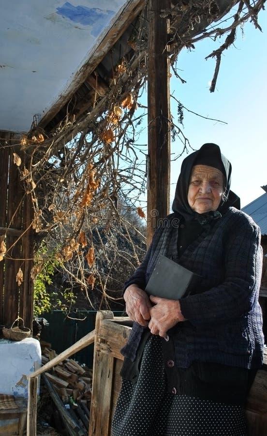 Signora anziana triste che tiene una bibbia sul suo portico immagine stock libera da diritti