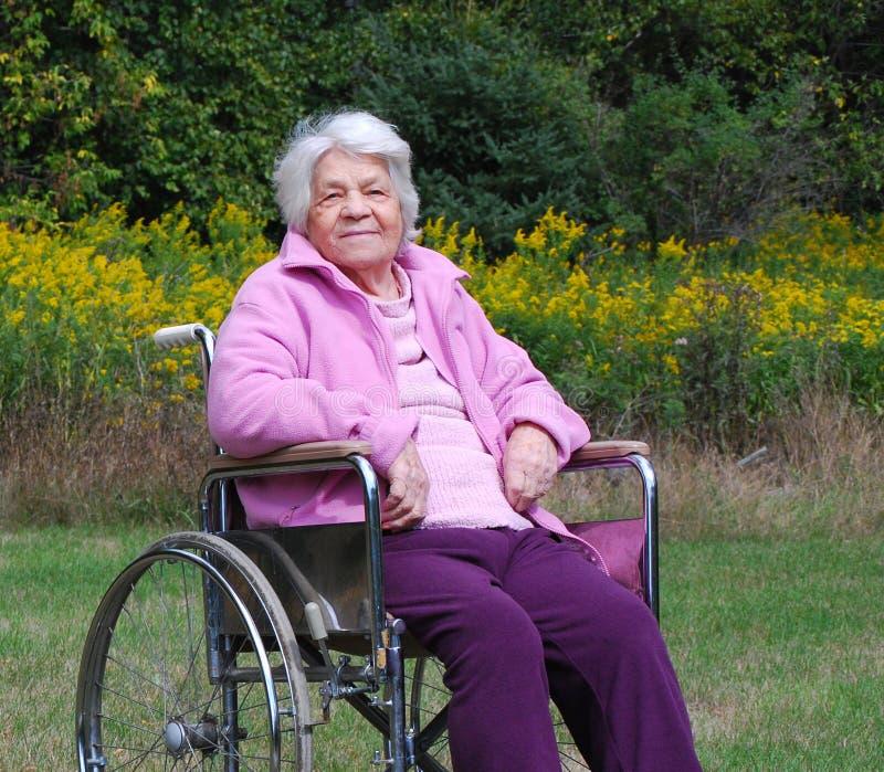 Signora anziana in una sedia a rotelle fotografie stock
