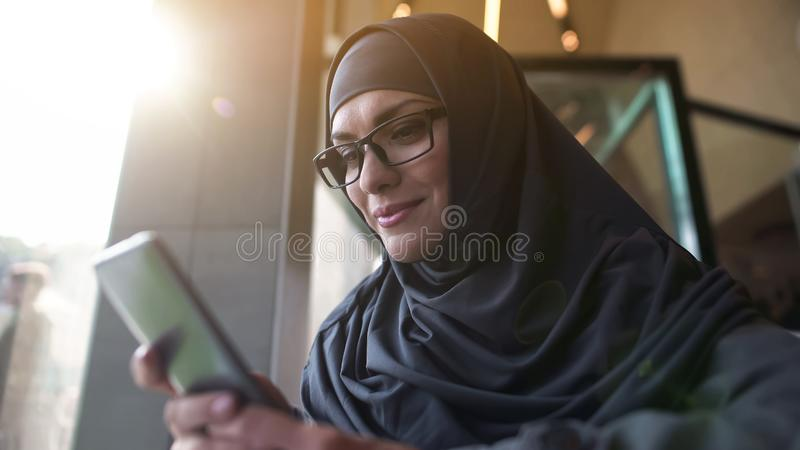 Signora araba sorridente in caffè che chiacchiera sul telefono, domanda di acquisto online fotografia stock libera da diritti