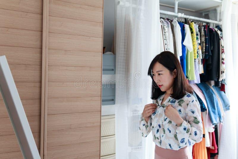 Signora asiatica che si prepara per uscire davanti allo specchio fotografia stock