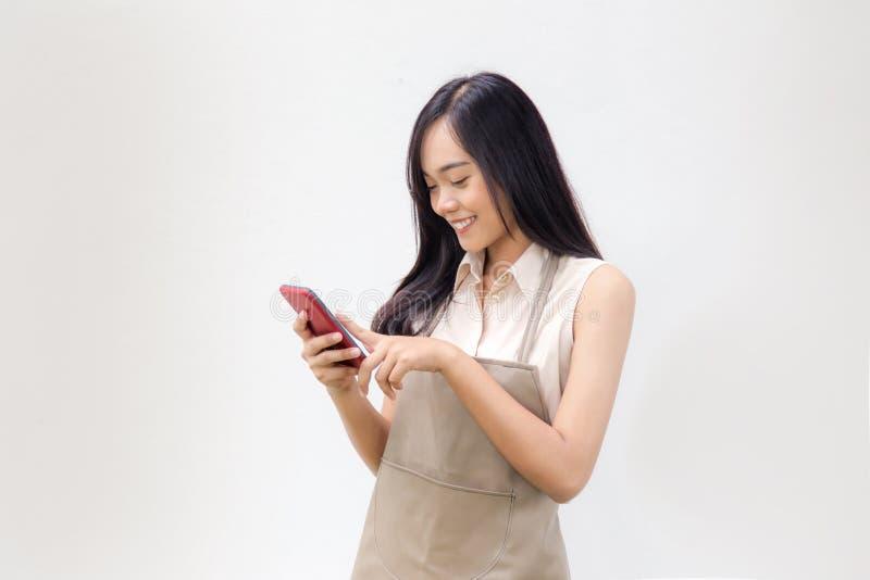 Signora asiatica con lo sguardo del vestito dal grembiule allo schermo mobile immagini stock