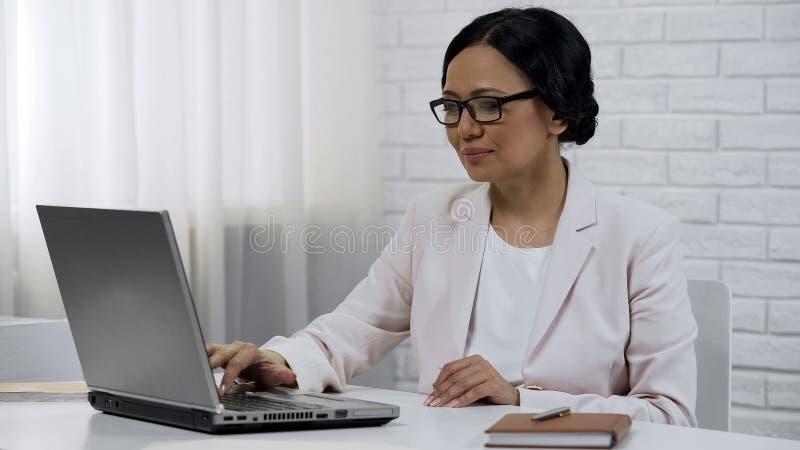 Signora asiatica di affari che scrive sul computer portatile, partenza d'inizio, riuscito progetto fotografia stock