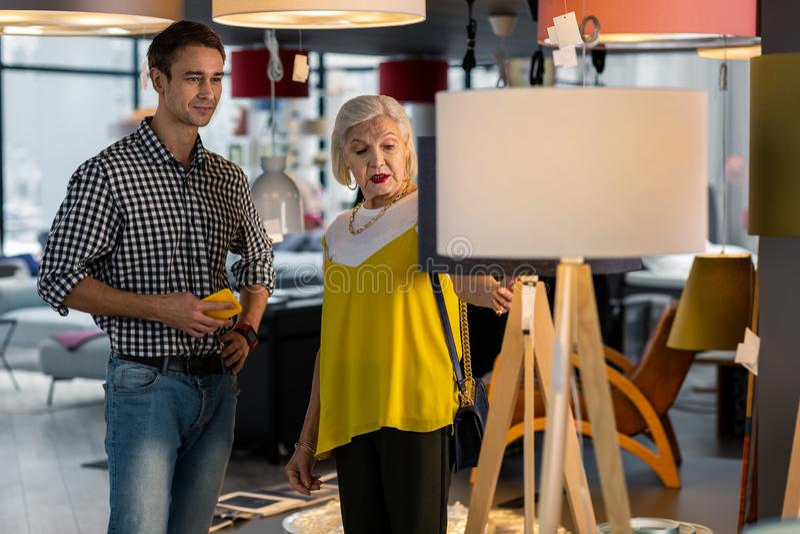 Signora attraente anziana che sceglie pavimento-lampada con il giovane uomo bello fotografia stock