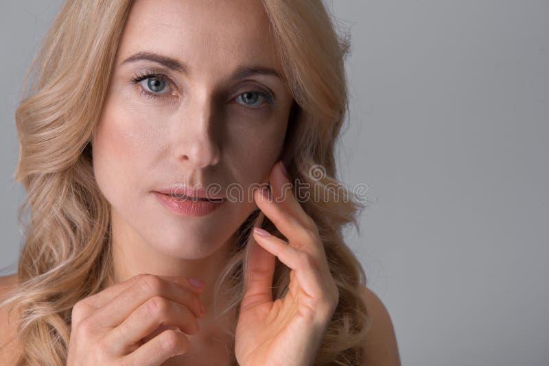 Signora attraente elegante sta posando meditatamente fotografia stock libera da diritti