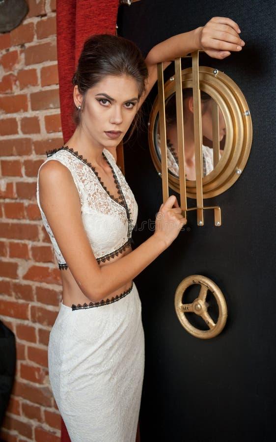 Signora attraente sensuale alla moda con il vestito bianco che sta vicino ad una cassaforte in una scena d'annata Donna del brune fotografia stock libera da diritti