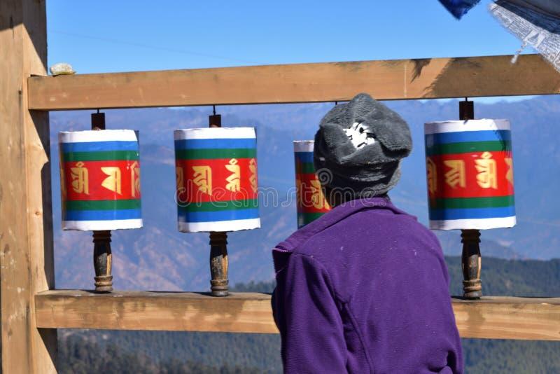Signora Bhutanese anziana e vecchie ruote di preghiera tibetane di legno al passaggio della La di Chele, Bhutan immagini stock libere da diritti