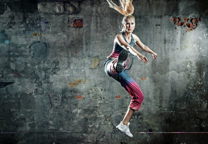 Signora bionda dell'atleta in una posa di salto immagine stock libera da diritti