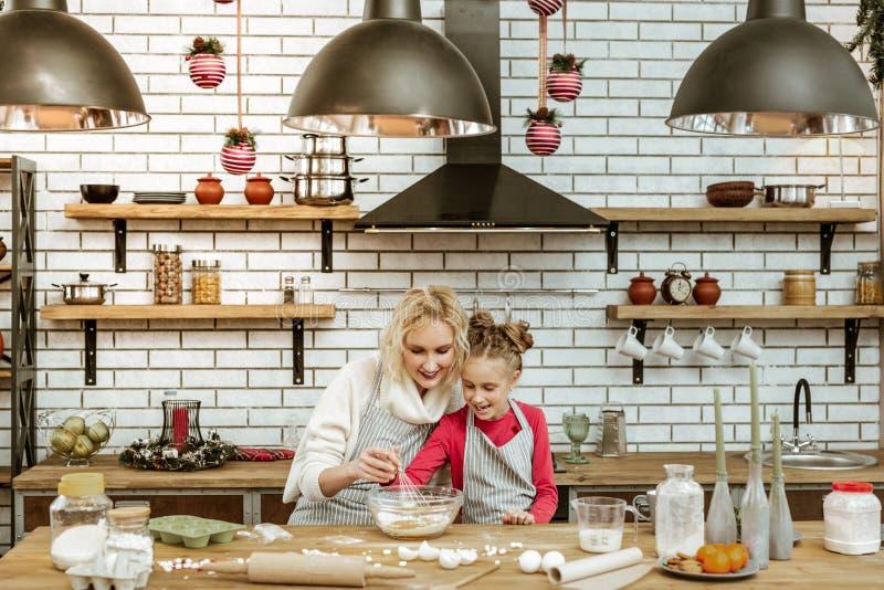 Signora bionda sorridente che si siede con la figlia in cucina riempita alla moda immagini stock libere da diritti