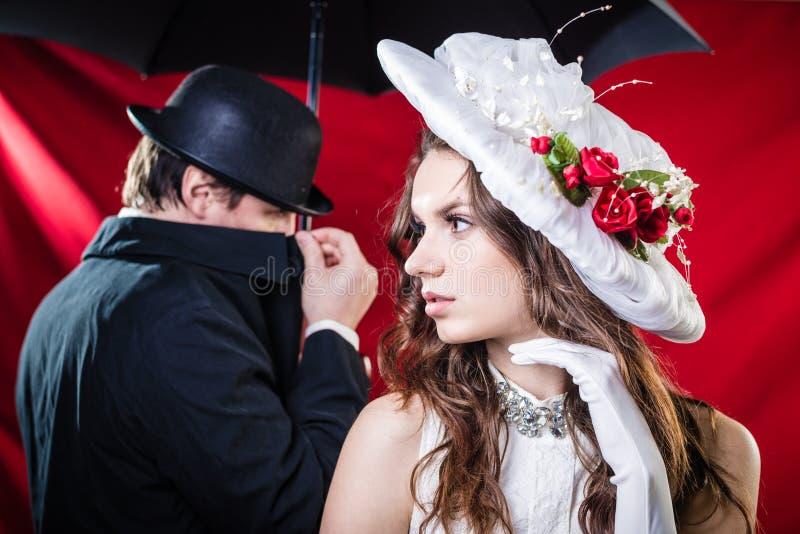 Signora in cappello ed in uomo misterioso nel nascondersi nero immagini stock