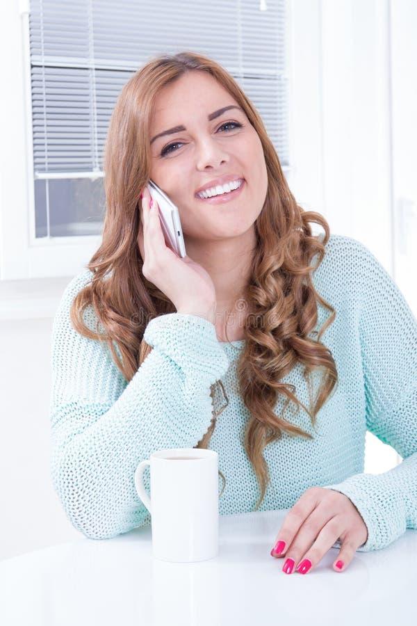 Signora caucasica con il telefono cellulare ed il caffè bevente immagini stock libere da diritti