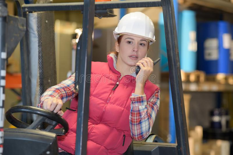 Signora che convince walkie-talkie mentre guidando carrello elevatore fotografia stock