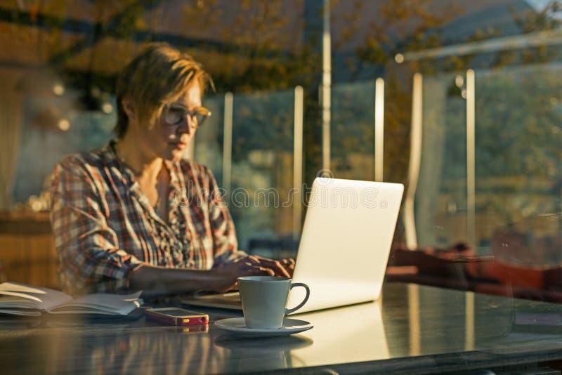 Signora che lavora al progetto indipendente nella vista della finestra del tiro del caffè immagine stock