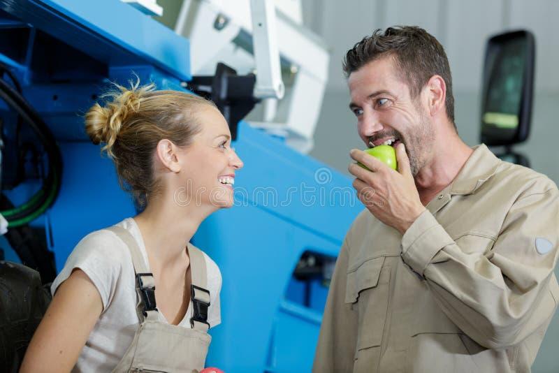 Signora che ride come morsi maschii del collega nella mela verde immagini stock