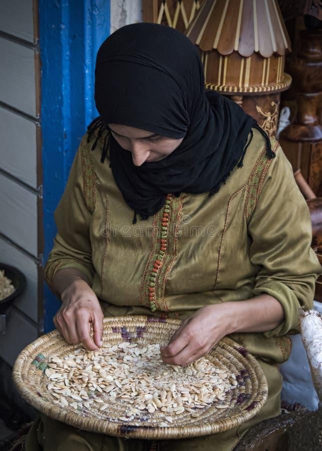 Signora che separa a mano tramite i dadi dell'argania spinosa che sono trasformati il petrolio per cibo o l'uso cosmetico fotografie stock