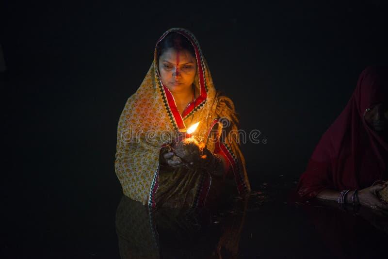 Signora che sta in acqua di fiume al puja del chhat immagine stock