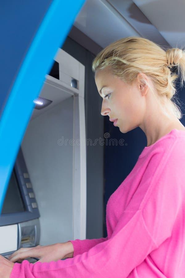 Signora che usando un contatore di bancomat immagini stock libere da diritti