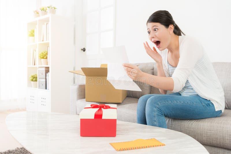 Signora colpita felice che disimballa la scatola personale del pacchetto fotografia stock