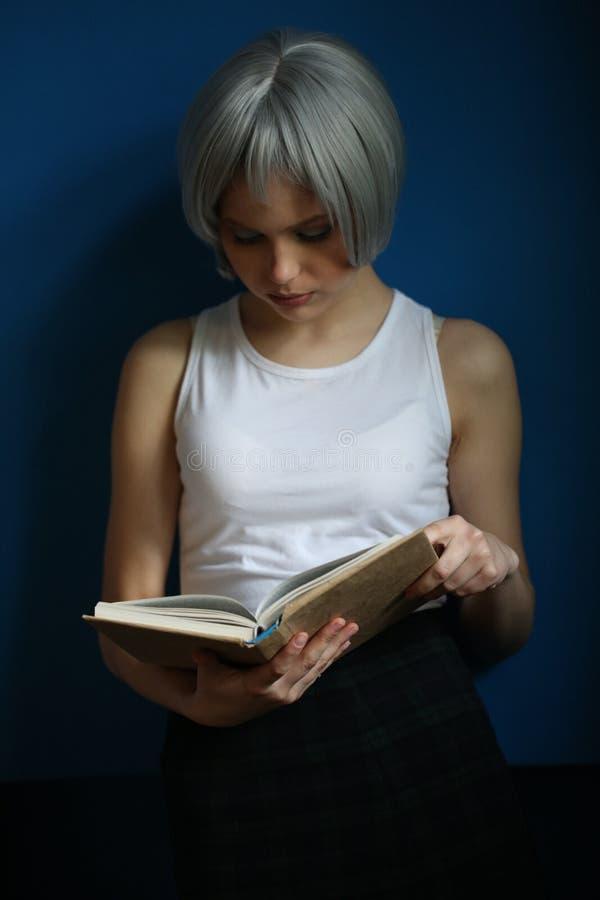 Signora con capelli d'argento che legge un libro e le candele Fine in su Priorità bassa per una scheda dell'invito o una congratu fotografia stock