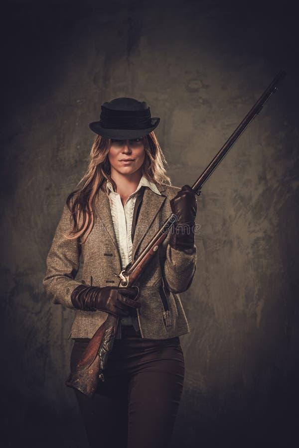 Signora con il fucile da caccia ed il cappello dall'ovest selvaggio su fondo scuro fotografie stock libere da diritti