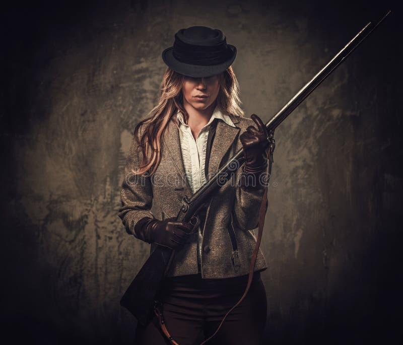 Signora con il fucile da caccia ed il cappello dall'ovest selvaggio su fondo scuro fotografie stock