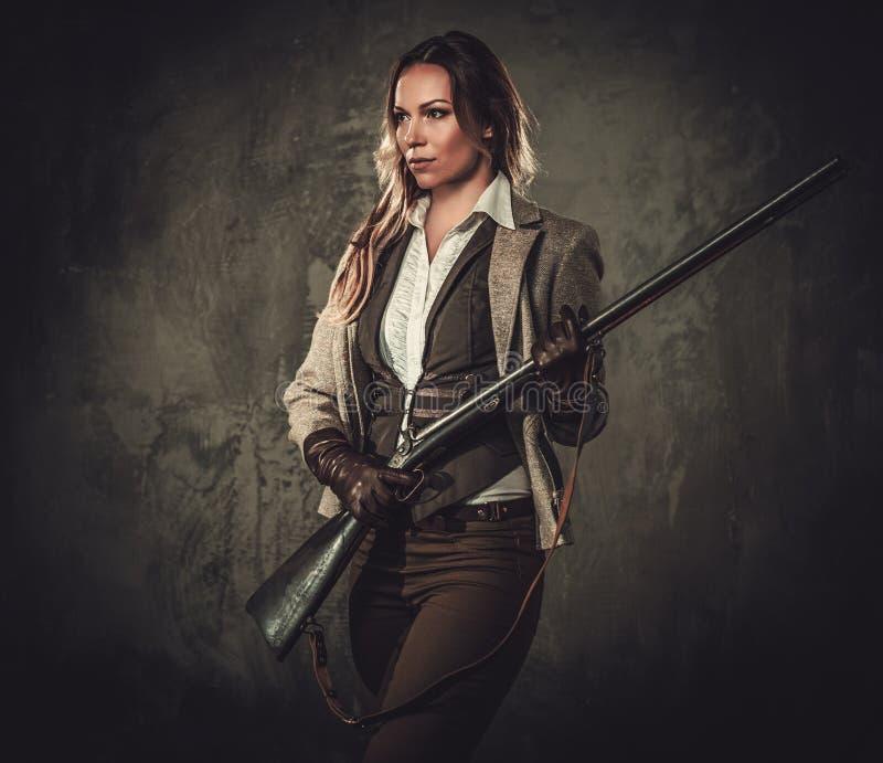 Signora con il fucile da caccia ed il cappello dall'ovest selvaggio su fondo scuro fotografia stock libera da diritti