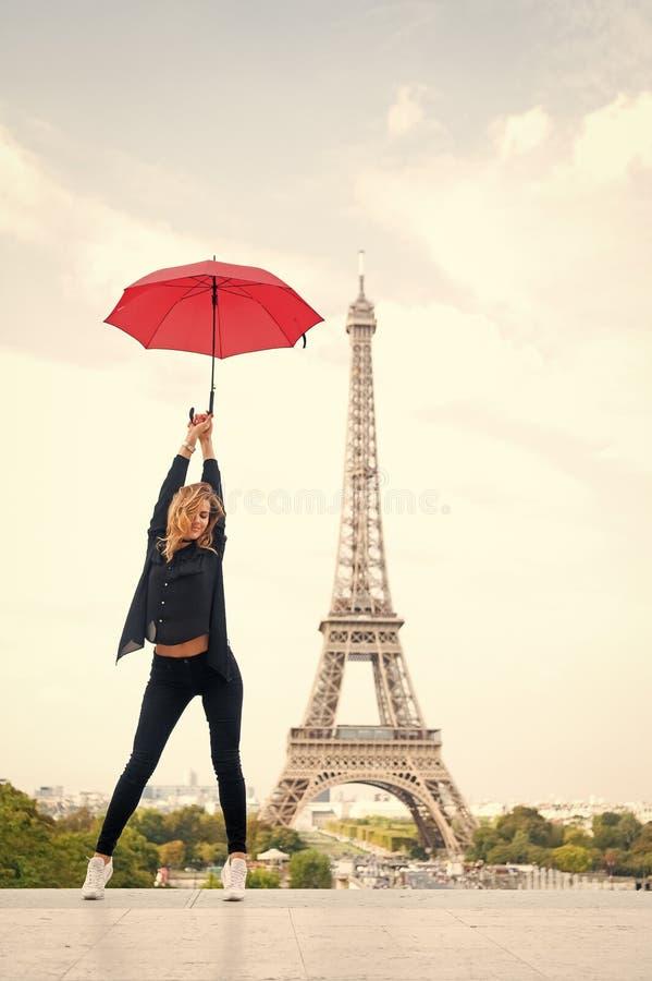 Signora con l'ombrello che posa davanti alla torre Eiffel, fondo del cielo Sportivo turistico e l'attivo di signora camminano nel fotografia stock libera da diritti