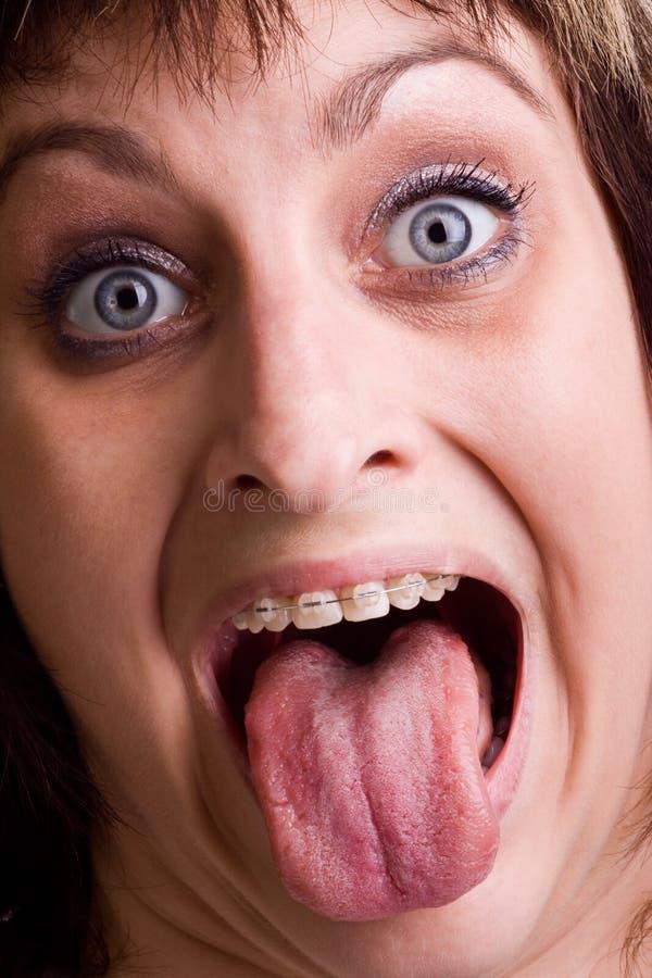 Signora con la linguetta fuori immagine stock