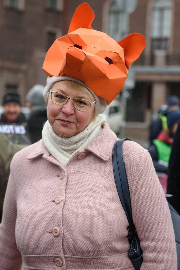 """Signora con la maschera della volpe della carta come cappello, durante """"marzo per gli animali a Riga, la Lettonia fotografie stock"""