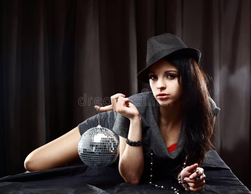 signora con la sfera lucida della discoteca, trovantesi sulla tabella immagini stock