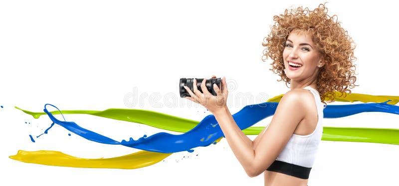 Signora crespo-dai capelli allegra che tiene un obiettivo lungo fuoco fotografie stock libere da diritti