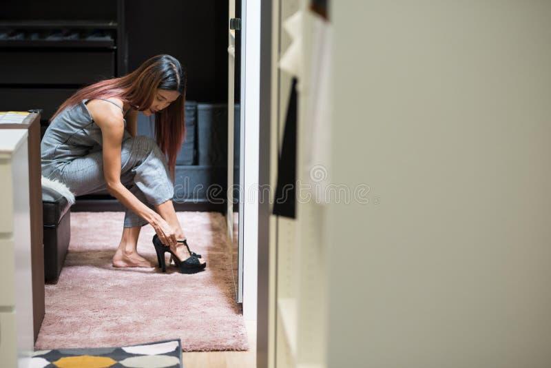 Signora dai capelli lunghi asiatica nel vestito di salto che prova sulle scarpe dalla l elegante fotografia stock