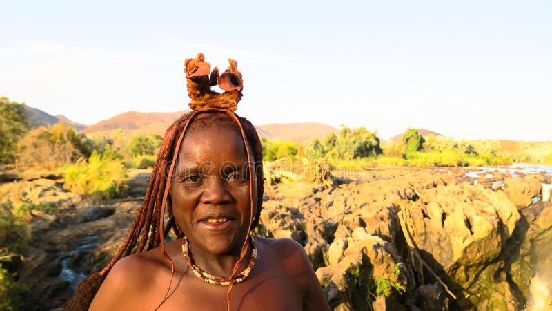 Signora davanti alle cadute di Epupa - Namibia - Africa di Himba immagini stock