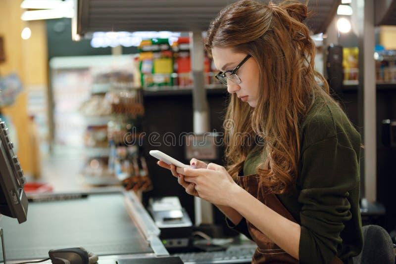 Signora del cassiere su area di lavoro nel negozio del supermercato facendo uso del cellulare fotografie stock libere da diritti