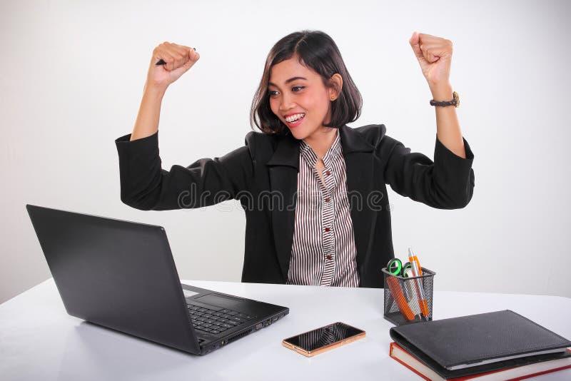 Signora dell'ufficio nella gioia che esamina un computer portatile su uno scrittorio, su fondo bianco immagini stock