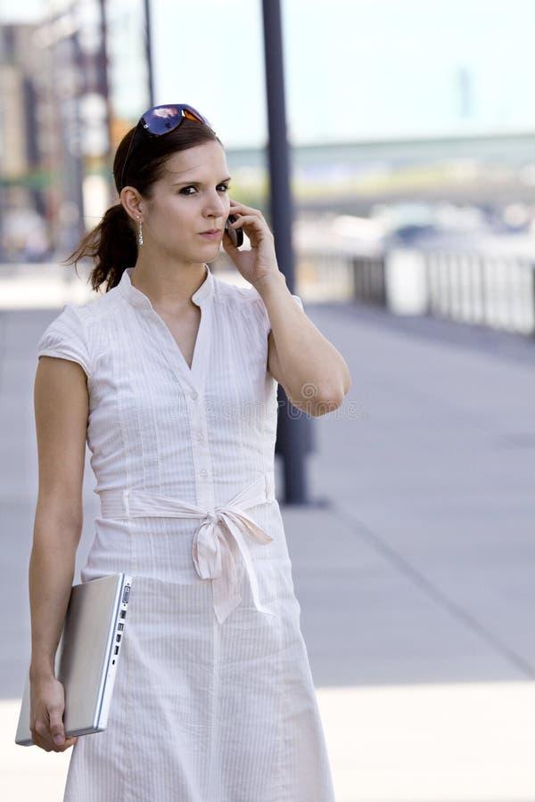 Signora di affari che cammina con il giro del telefono mobile immagini stock