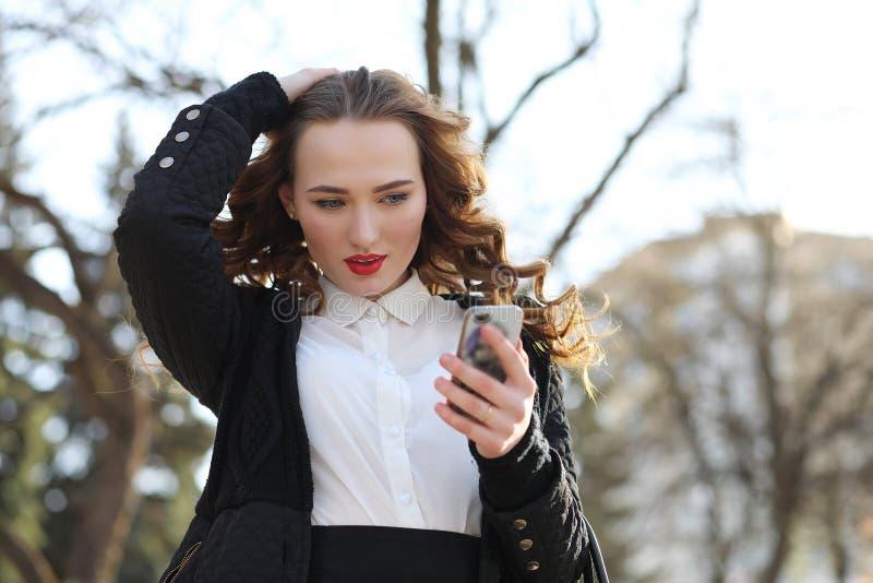 Signora di affari in un vestito all'aperto con il telefono cellulare immagine stock