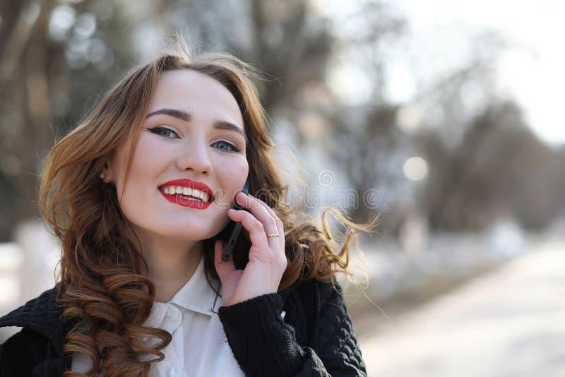 Signora di affari in un vestito all'aperto con il telefono cellulare fotografia stock