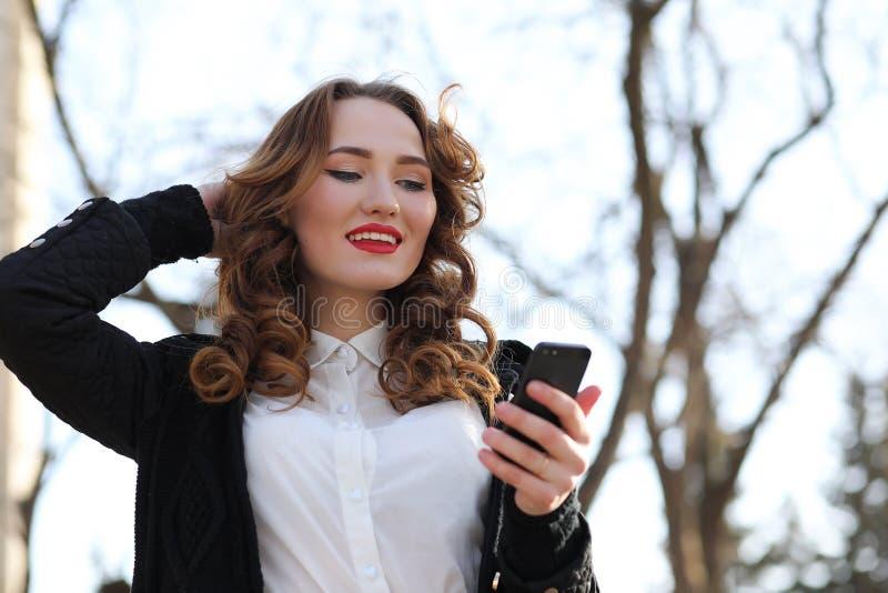 Signora di affari in un vestito all'aperto con il telefono cellulare fotografia stock libera da diritti