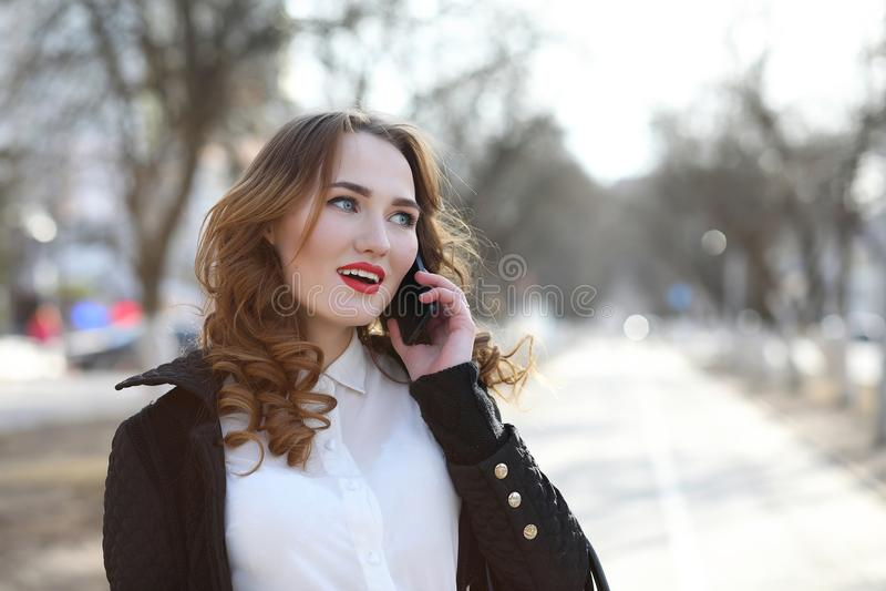 Signora di affari in un vestito all'aperto con il telefono cellulare immagine stock libera da diritti