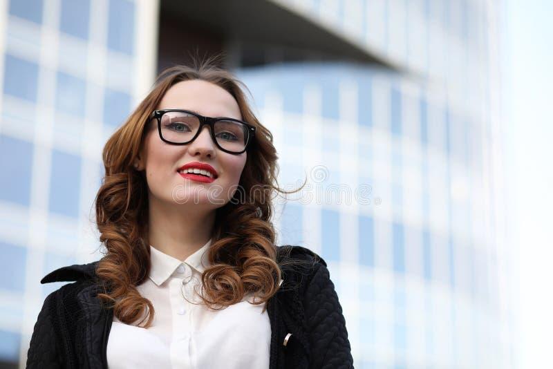 Signora di affari in vestiti rigorosi sui precedenti delle costruzioni fotografia stock