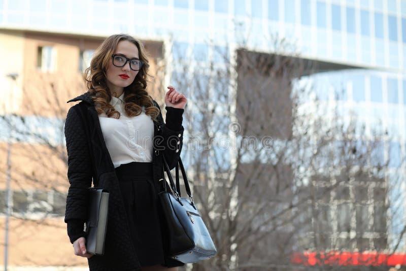 Signora di affari in vestiti rigorosi sui precedenti delle costruzioni immagini stock