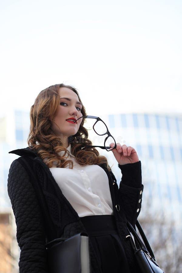 Signora di affari in vestiti rigorosi sui precedenti delle costruzioni immagini stock libere da diritti