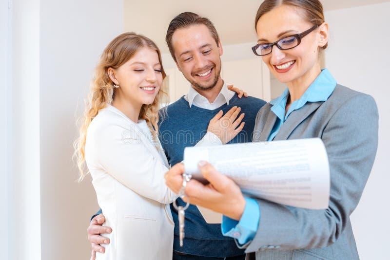 Signora di agente immobiliare che riempie in dettaglio sul nuovo contratto di contratto d'affitto per l'appartamento fotografie stock