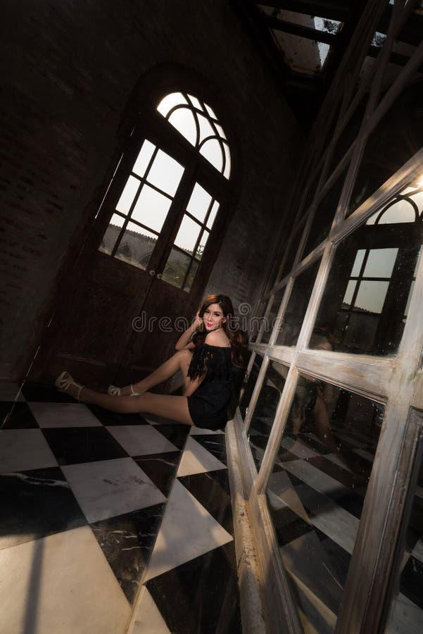 Signora di bellezza che si siede sul pavimento d'annata fotografia stock