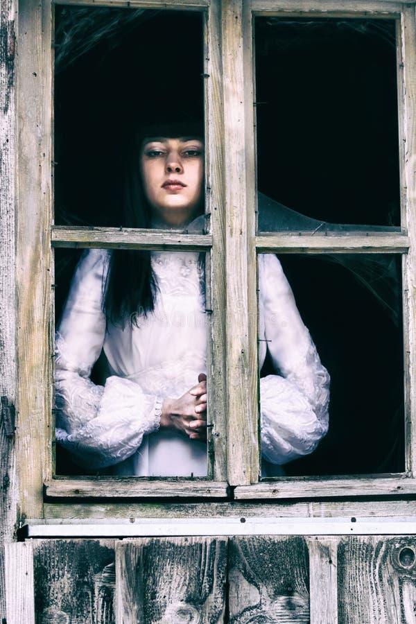 Signora di orrore alla finestra fotografia stock