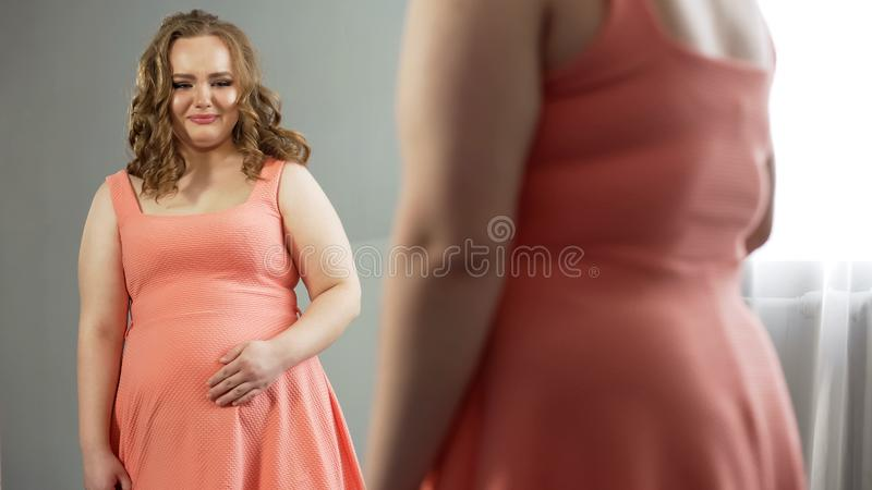 Signora di peso eccessivo insoddisfatta della sua riflessione di specchio, depressione della fase della placenta immagine stock