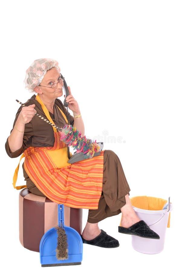 Signora di pulizia sul telefono fotografia stock libera da diritti